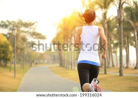 woman runner athlete running at tropical park - stock photo