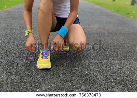 woman runner athlete tying shoelace at tropical park