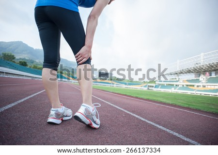 woman runner hold her injured leg on track - stock photo