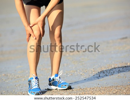 woman runner hold her sports injured knee  - stock photo