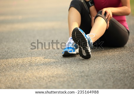 woman runner hold her sports injured knee outdoor  - stock photo
