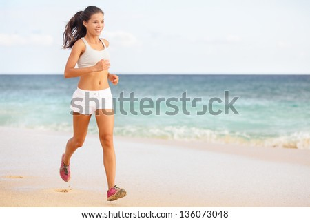 Woman runner jogging or running on beach training in barefoot sport shoes. Beautiful young fit fitness model in working out outside in summer wearing shorts. Mixed race Asian / Caucasian female girl - stock photo