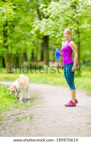 Woman runner running and walking with dog in park, summer nature, exercising in bright forest outdoors - stock photo