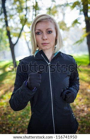 Woman runner running in autumn forest. Young girl jogging in fall colors.