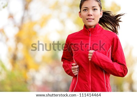 Woman runner running in autumn forest. Young mixed race girl jogging in fall colors. - stock photo