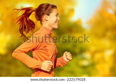 Woman runner running in fall autumn forest. Female fitness girl jogging on path in amazing fall foliage landscape nature outside. - stock photo