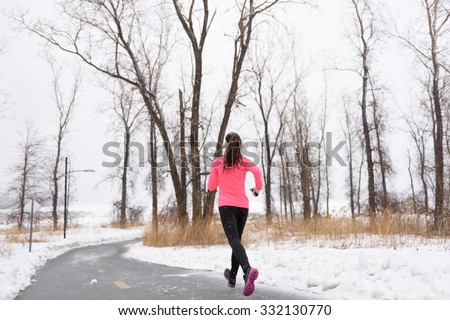 Woman runner running in winter snow - active lifestyle. Female athlete from the back jogging training her cardio on city park path outside in cold weather wearing leggings and coat. - stock photo