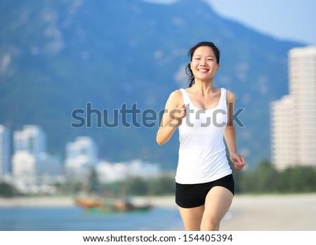 woman runner running on beach - stock photo