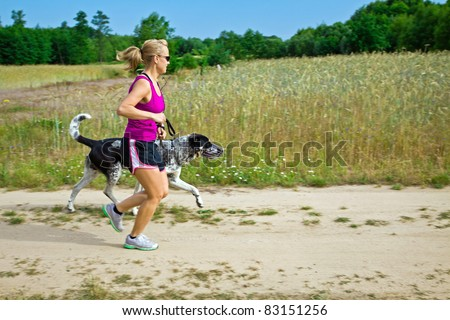 Woman runner running with a dog on country road - stock photo