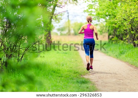 Woman runner running with dog in park on country road, healthy lifestyle and training working out outdoors, exercising in bright colorful environment. Inspirational and motivational concept.