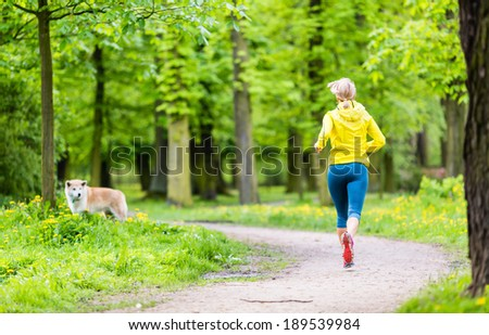 Woman runner running with dog in park, summer nature, exercising in bright forest outdoors - stock photo