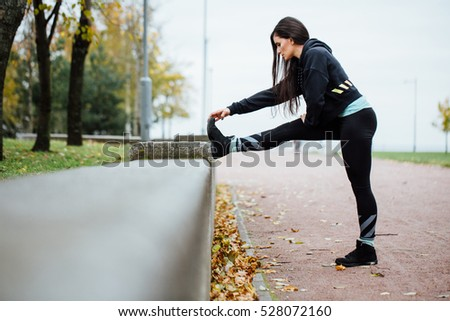 Woman runner stretching legs before run. Beautiful young athlete woman working out. Fitness concept. Side view.