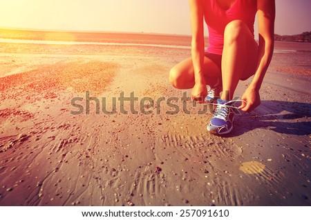 woman runner tying shoelace before running on beach - stock photo
