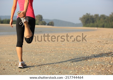 woman runner warm up before taking a jogging on beach - stock photo