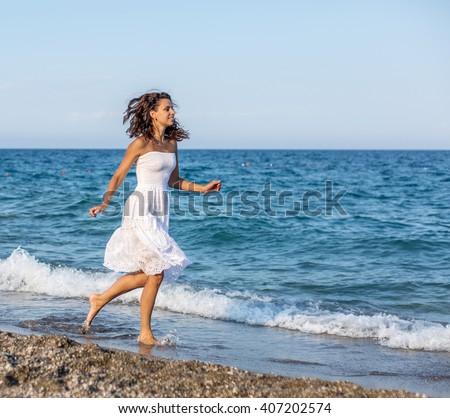 Woman running along the beach.  - stock photo