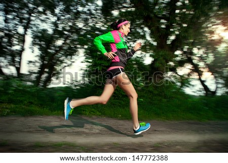 woman running along the terrain trail - stock photo