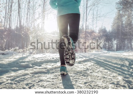 Woman Running at snowly winter under sunlight. - stock photo