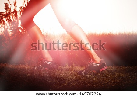 woman running at sunrise with muscular legs - stock photo
