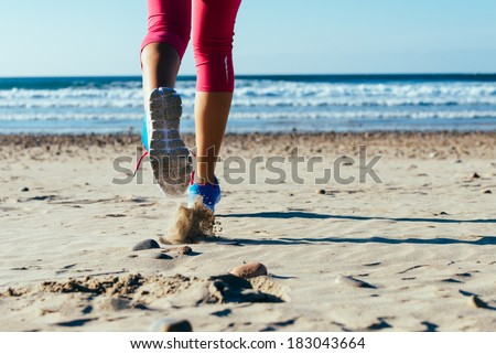 Woman running fast on beach. Female runner legs and sport footwear detail. - stock photo