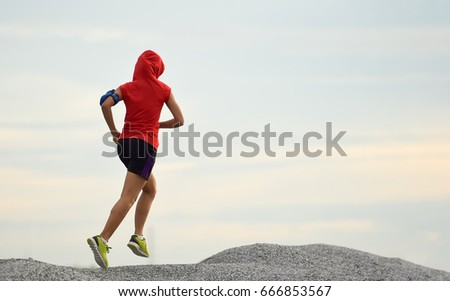 Woman running. Female runner jogging, training for marathon. Fit girl fitness athlete model exercising outdoor.