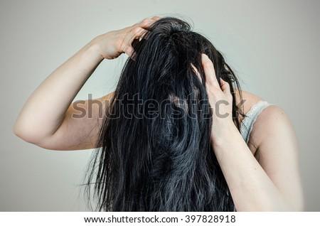 Woman running her fingers through her hair scratching her scalp. Landscape. - stock photo