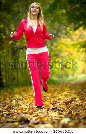 Woman running in autumn fall forest. Female runner training outdoor. Healthy lifestyle young blonde girl jogging outside. Yellow autumnal leaves.