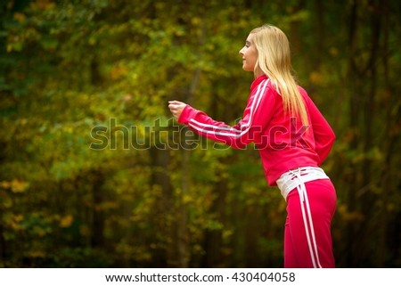 Woman running in autumn fall forest. Female runner training outdoor. Healthy lifestyle young blonde girl jogging outside. Yellow autumnal leaves. - stock photo