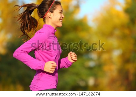 Woman running in autumn fall forest. Female runner training outdoor in profile. Healthy lifestyle image of young Asian woman jogging outside. Fit ethnic Asian Caucasian fitness model. - stock photo