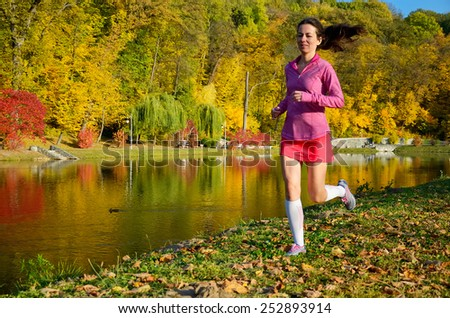 Woman running in autumn park, beautiful girl runner jogging outdoors, training for marathon, exercising and fitness concept  - stock photo