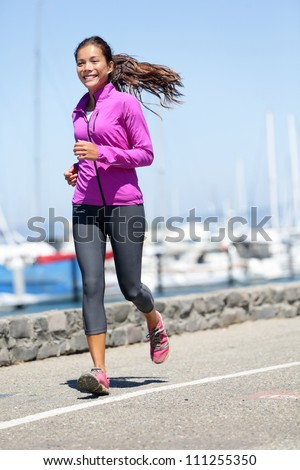 Woman running in fall / autumn running clothing outfit. Smiling happy female athlete runner training on waterfront harbour pier in San Francisco, California, USA. Mixed race fit fitness sport model. - stock photo
