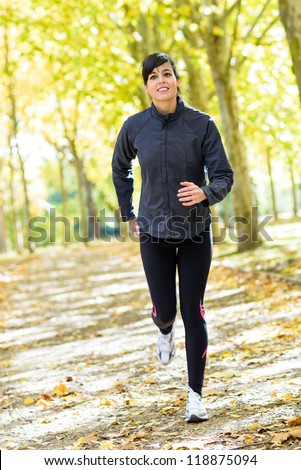 Woman running in park. Female athlete jogging on autumn day. Sport fitness brunette model training outdoor. - stock photo