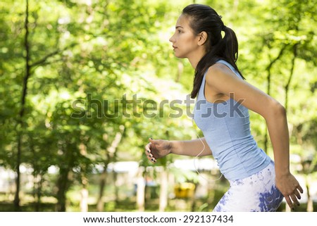 Woman running in summer forest. Female runner training outdoor in profile. Healthy lifestyle image of young woman jogging outside. Fit Caucasian fitness model. - stock photo