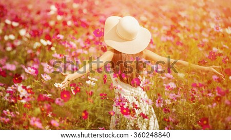 Woman running in the garden flowers Cosmos flowers to touch her. On a clear day - stock photo