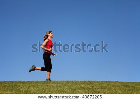 woman running in the green grass (with copy space)