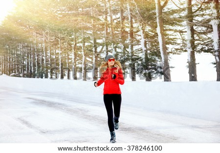 Woman running in the winter park, doing exercise in cold frosty morning, workout outdoors, healthy lifestyle, wintertime sport  - stock photo