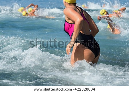 Woman running in water in the swimming competition in the background a group of swimmers - stock photo