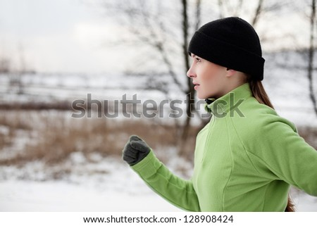 Woman running in winter - stock photo