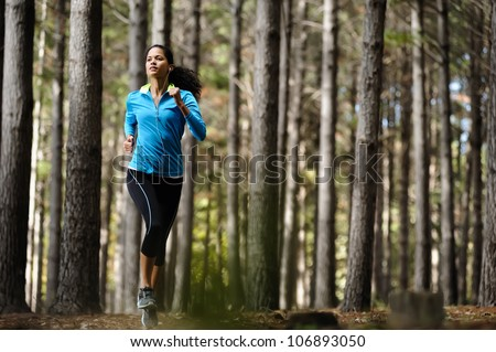Woman running in wooded forest area, training and exercising for trail run marathon endurance. Fitness healthy lifestyle concept. - stock photo