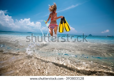 Woman running into the tropical sea with fins and snorkeling gear - stock photo