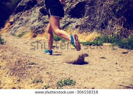 woman running on a dirt trail during the daylight while kicking up dust and dirt with shallow depth of field and instagram retro filter while in movement