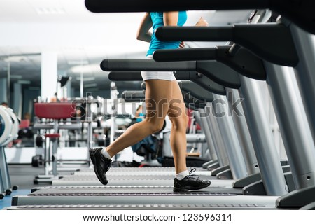 woman running on a treadmill in a fitness club, sport in the fitness club - stock photo