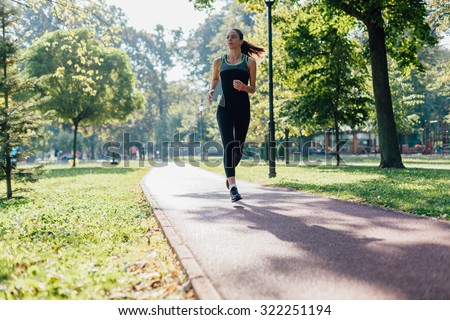 Woman running on jogging path in the park - stock photo