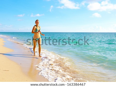 Woman running on Miami beach. Vacation.