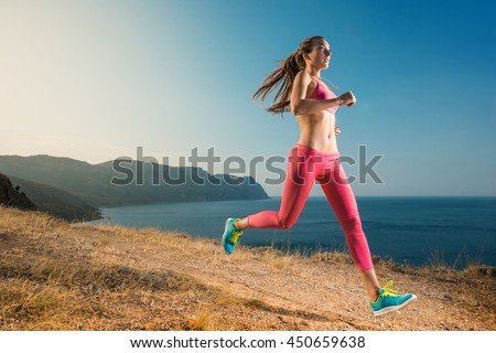 Woman running on mountain trail. Young runner jogging sneakers in a beautiful nature. Healthy lifestyle fitness.