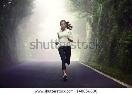 Woman running on road. Female runner jogging on mountain road training for marathon. Fit girl fitness athlete model exercising outdoor. - stock photo