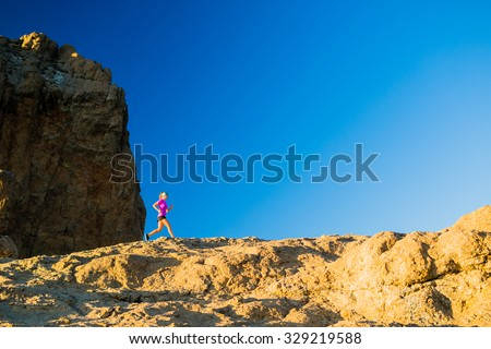 Woman running on rocky mountains, training and working out in beautiful inspirational mountain landscape. Fitness and exercising, cross country runner jogging. - stock photo