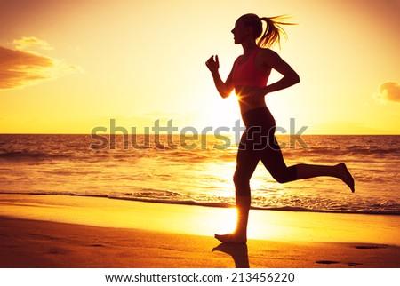 Woman running on the beach at sunset - stock photo
