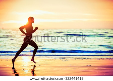 Woman running on the beach at sunset - male version in portfolio - stock photo