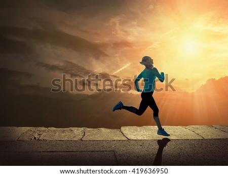 Woman running on the coastline under sunlight. - stock photo