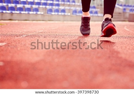 Woman running on the track on a sunny spring day. Woman running concept. Runner jogging training workout  - stock photo